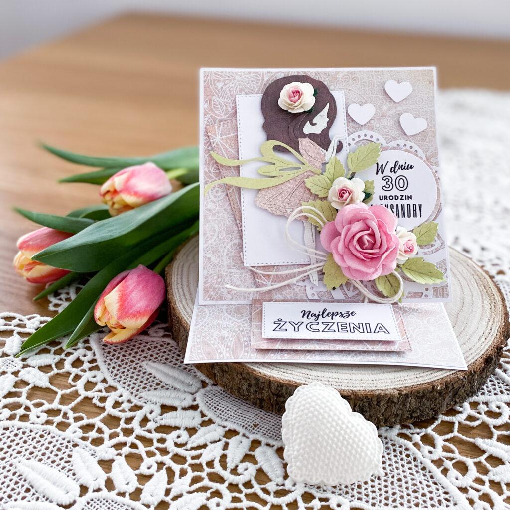Ręcznie wykonana kartka na 30 urodziny. Kartka jest w kolorze brudnego różu. Głównym motywem jest dziewczynka z serduszkami.