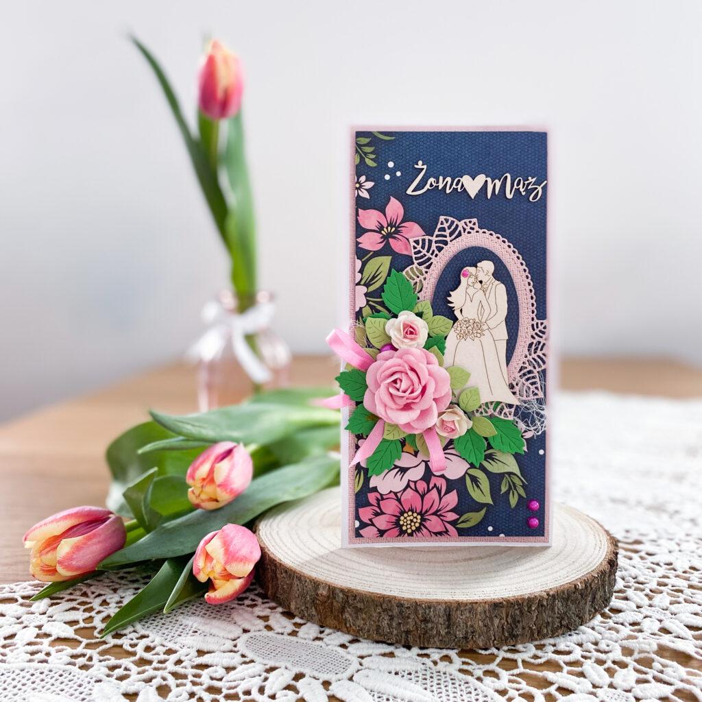Ręcznie wykonana kartka ślubna w granatowo-różowej kolorystyce, ozdobiona rozbudowaną kompozycją kwiatową.