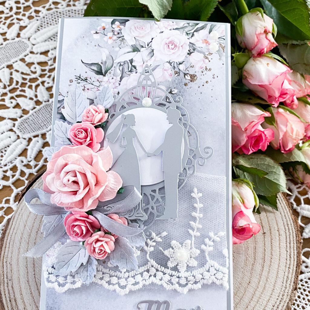 Ręcznie wykonana kartka ślubna w formacie DL. Cała w szaro srebrno różowej kolorystyce. Ozdobiona papierowymi różami, koronką i perełkami.